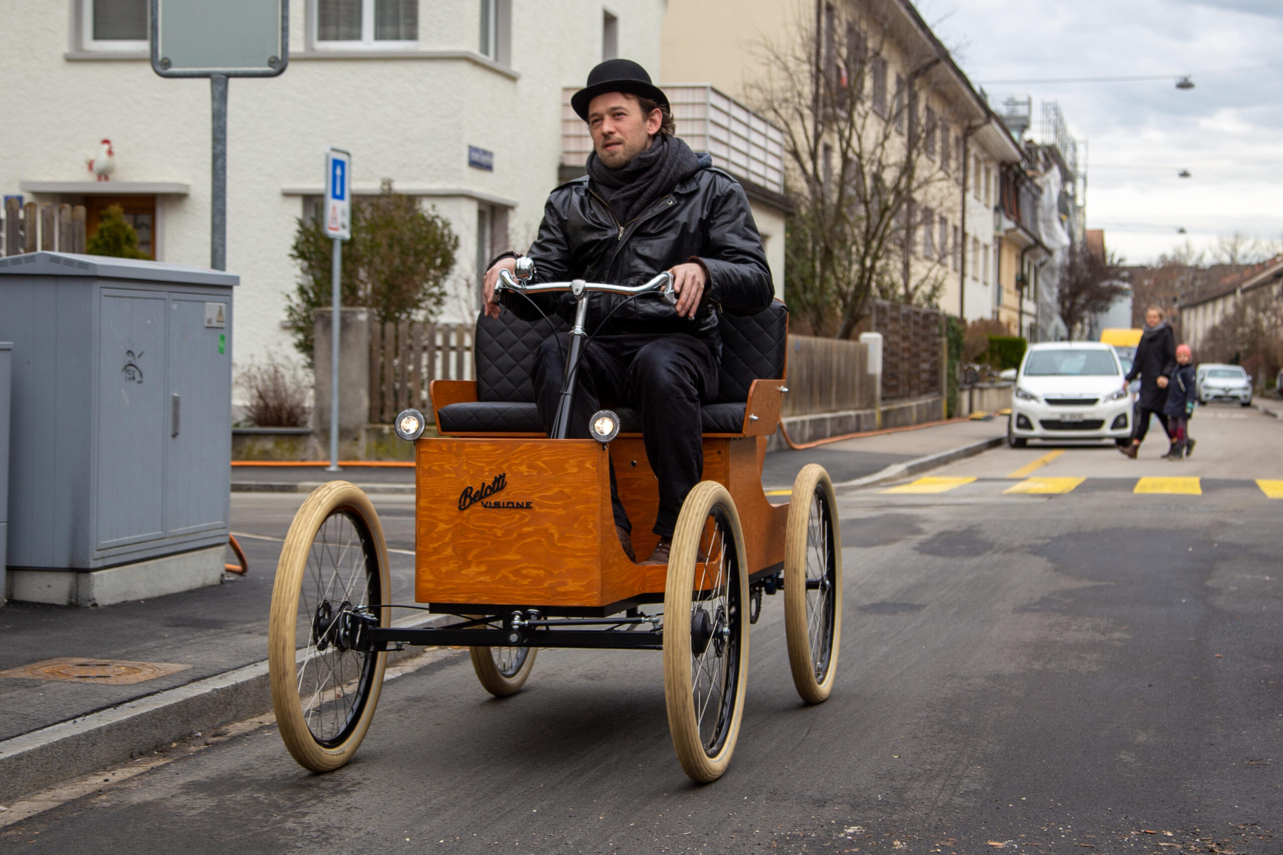 A man in black with a bowler sits on an oldtimer and enjoys driving